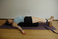 Setu Bandha - bridge pose, supported by a bolster (belt on legs is optional)