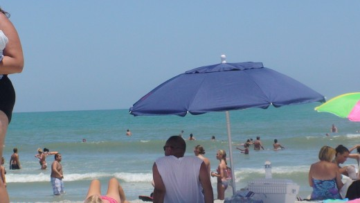 Beach umbrellas provide welcome shade from the hot sun.