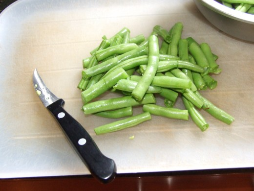 Cleaning the ends of the green beans.