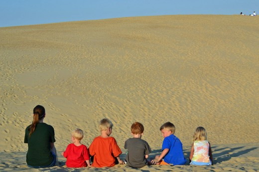 Jockey's Ridge State Park: The kids sitting at the top of one sand dune peering at the top of another