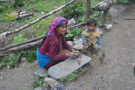 A mother in rural Nepal cracks walnut for her son