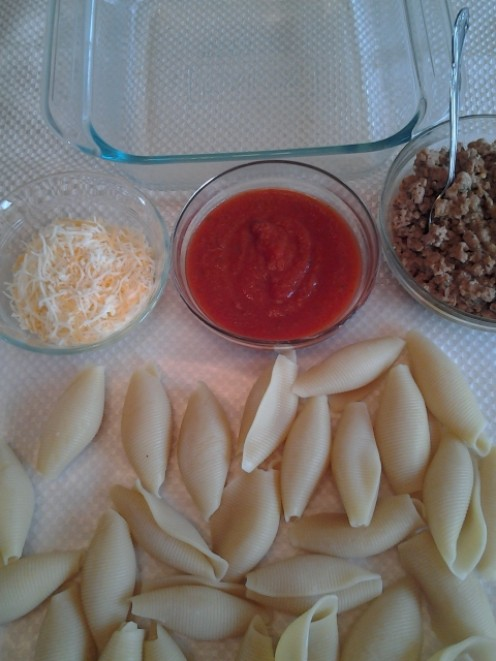 Cooked pasta shells with cheese, sauce and sausage
