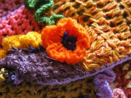 DESCRIPTIONCloseup of an orange crocheted flower with a multi-colored crochet fabric background.