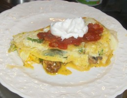 Filled omelet topped with salsa and sour cream.