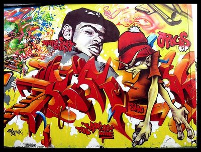 The sharp interlacing letters are sprayed in front of an imalgamation of real life and cartoon characters.  This is a typical 'piece' depicting Hip-hop graffiti