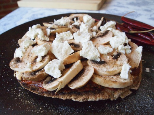 Layer with loads of mushrooms and just the right amount of goat cheese. The fresh and dry  creamy lumps of goat cheese add a second dimension to this healthy homemade pita pizza.