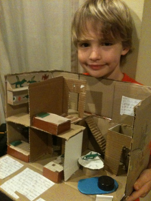 Diorama made from corrugated cardboard, cereal box cardboard, magazine cutouts, bottle caps, styrofoam scraps, and small boxes.