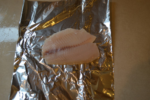 Thawed tilapia on foil