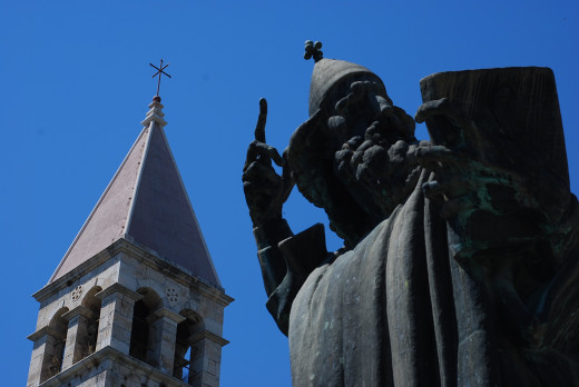 Ivan Meštrović sculpture from 1929.  Ninski is famous for preaching Croatians in their native tongue during 10th c, not Latin which no one understood.  Located near the north wall near the tower of Bl. Arnir, Split Archbishop.