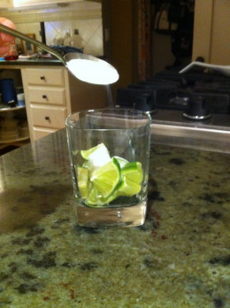 Adding sugar to the limes placed in a tumbler.