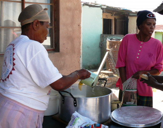 Mercy and Francina squeezing the last drop of soup out of the pot