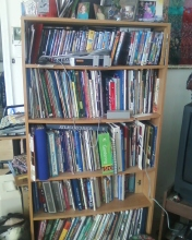 This bookshelf is filled with gardening, quilting, writing, health and other books. The top shelf is filled with DVDs.