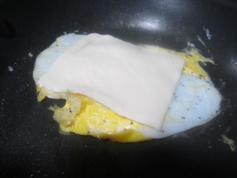 Add cheese to egg in pan to melt slightly.