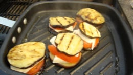Once they are assembled, flipping is unneccessary.  Simply cover for a couple of minutes to allow the cheese to melt.