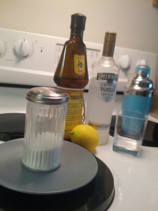 From Left to Right: Sugar, Plate, Lemon, Frangelico, Vanilla Vodka, Glass and Shaker.