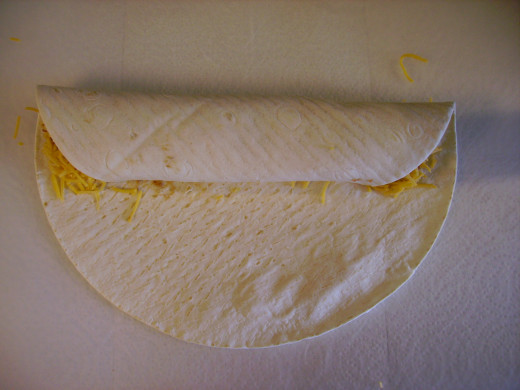 Roll up tortilla carefully. Place enchilada in the pan with the exposed end down, so it won't unroll.