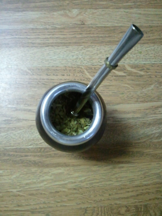 The bombilla is pushed into the slope of wet yerba mate.