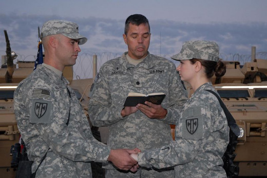 Sgt. Joshua Klassen, a native of Pocatello, Idaho and Lori Klassen, a native of Portland, Ore., both members of Headquarters and Headquarters Company 18th Military Police Brigade hold hands as their marriage vows are blessed by Chaplain (Lt. Col.)