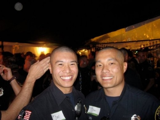 After getting their heads shaved, two of the firefighters smile and show off their new bald look.