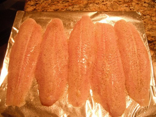 Fish fillets have been placed on a foil-covered pan, brushed with butter and lightly sprinkled with lemon pepper. Yes, the prep is that easy!