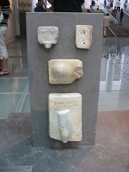 Relief votive offerings from the Asclepieion 4th century BC.    a) Eyes (top left)  b) An ear (top right)  c) A breast and an inscription to Asclepios         (center)  d) A leg and an inscription (bottom)