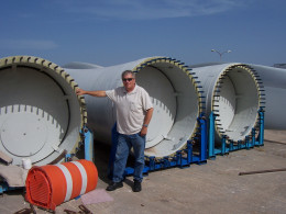 Picture of Kent Britain, the author's father, used with his permission. Kent is standing next to a wind power turbine before the blades have been attached.  Installing renewable energy sources can add back up power sources when the main grid is down.