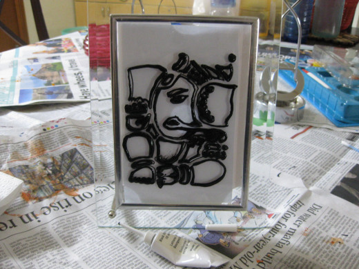 The outline of God Ganesh on the photograph-frame, using a black out-liner tube.