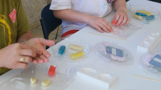 Visitors use pre-colored marzipan logs to fashion shapes and designs using silicone molds, a rolling pin, and a pointy stick.