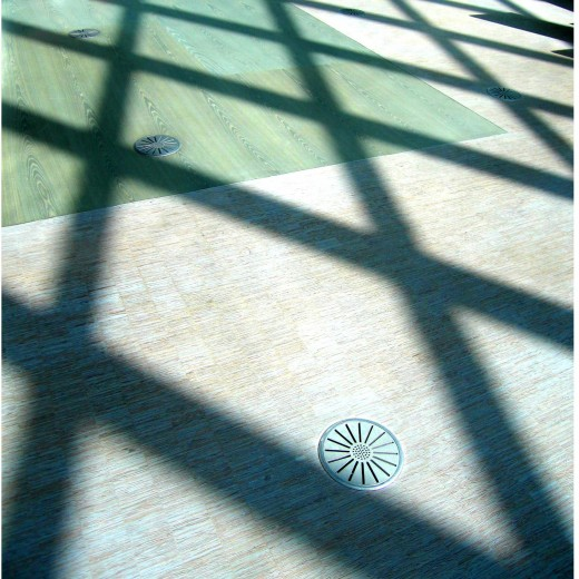 dramatic diamond shadows on flooring made from wood scraps and elegant round registers