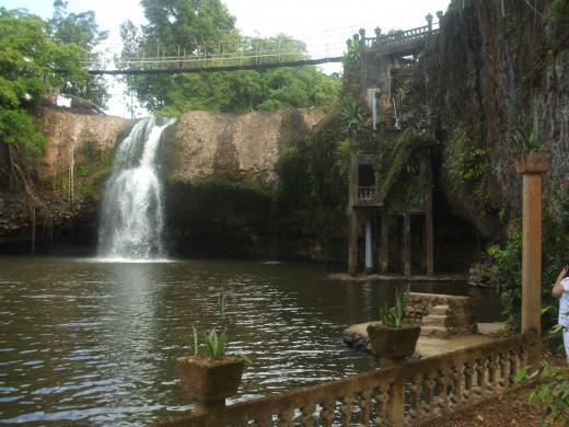 Mena Creek Waterfall with swing bridge leading to picnic area.
