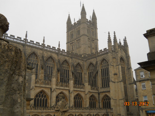 Bath Abbey towers over the Roman Bath museum.