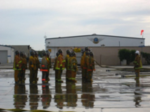 Fire academy recruits practice hose lays.