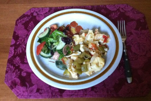 Cheese tortellini with veggie topping and a side salad.
