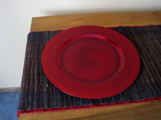 Red charger plate on layered table runners.