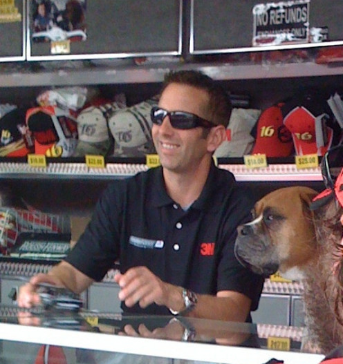 NASCAR driver Greg Biffle signing autographs at Richmond with his dog at his side.