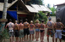 Tourists mark their bodies with marker to show their love for the wild little hostel