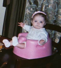 Faith's Grand daughter Lily sitting on top of the table in her pink Bumbo seat
