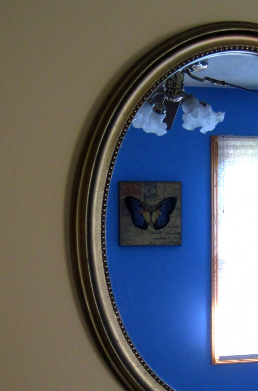 Gold oval mirror reflects the rich blue interior.