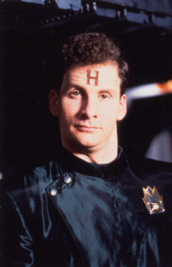 Arnold Rimmer.  The H on his head stands for 'Hologram' - he ain't real.