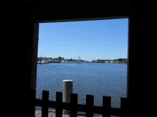 A view out of the Tom Claggett Boat Shed onto the Mystic River, with the current town of Mystic,CT in the background.
