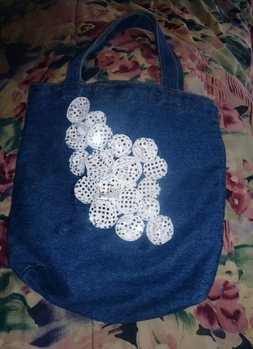 Denim tote with white sequin fabric embellishments. These are multiple layered flowers.