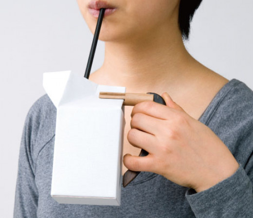 Photo of Girl Drinking from Milk Carton with Handle