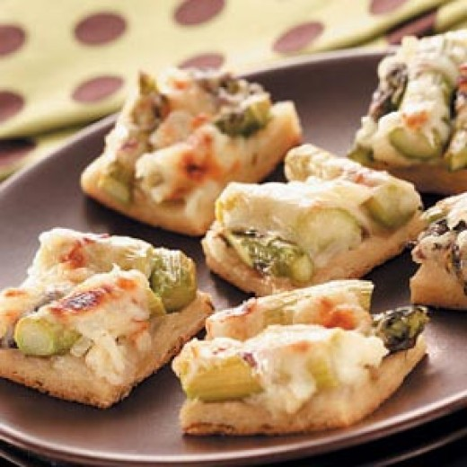 Bit-sized croissant pizza squares with asparagus and cheese on top.