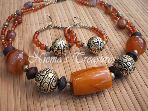Brazillian Sunset; large African Amber focal point bead compllimented with Carneilan, wood and brass.