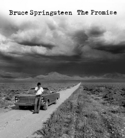 "The Cover of ""The Promise"" an album of ""Darkness on the Edge of Town"" outtakes. Released 2010. Great Photo by Eric Meola showing Bruce on a desert road, with  a classic American car and growing storm clouds.courtesy of Columbia Record"