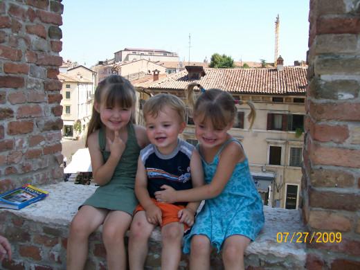 My three kids sitting on the wall overlooking part of Verona
