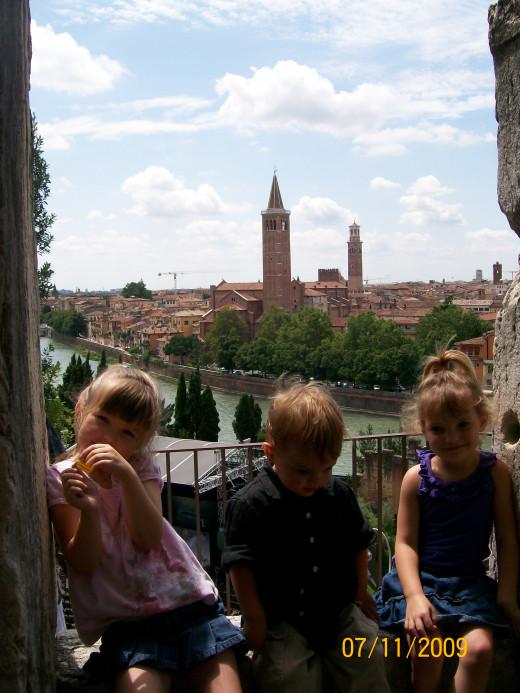 My three kids sitting on the wall overlooking Verona