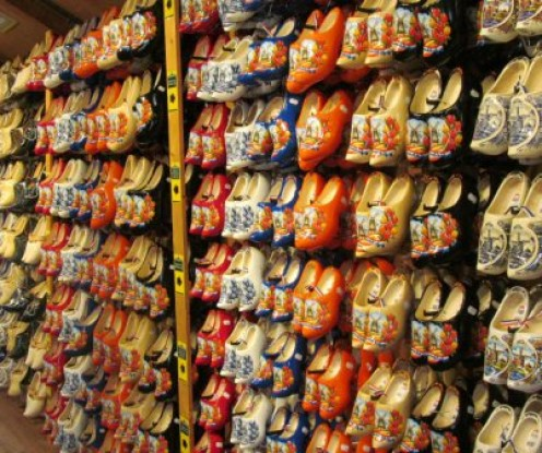 To buy wooden shoes at Zaanse Schans is somewhat less expensive than in Amsterdam.  You will have a wide variety to choose from.