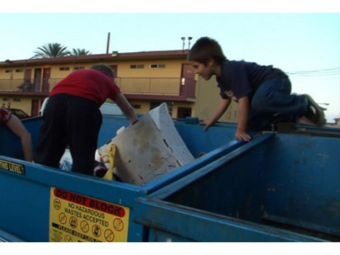 These Orange County, California kids live in the bed-bug infested motel seen in the background. They are pictured digging in the dumpster for their 'new' toy.