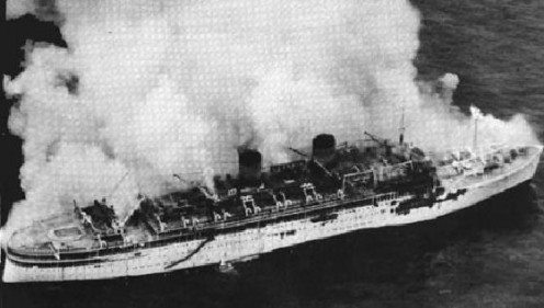 Aerial photo of TSMS Lakonia (1929-1963) burning. Caught fire and sank in 1963.